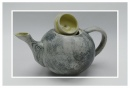 yellow ceramic teapot with upturned lid